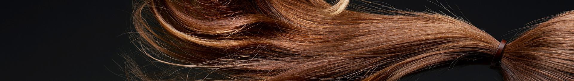 Brązowe włosy na ciemnym tle