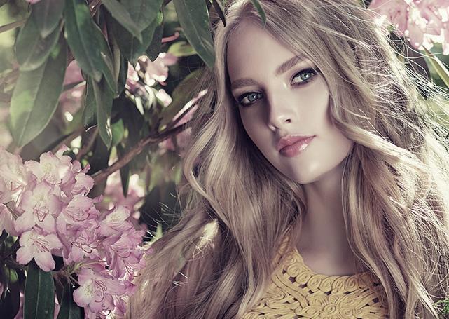 Kobieta zjasnymi włosami natle kwiatów